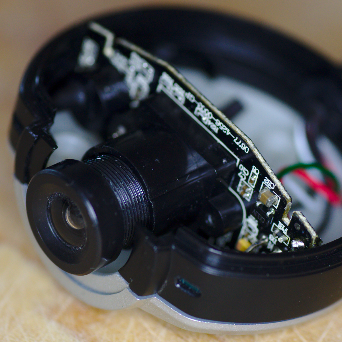 the webcam with the top part of the case removed  the case turns out to be  mostly empty, with just one small circuit board to which the lens is  attached